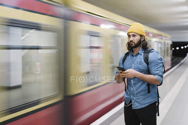 Retrato de homem ouvindo música com fones de ouvido e smartphone enquanto espera na plataforma, Berlim, Alemanha — Fotografia de Stock