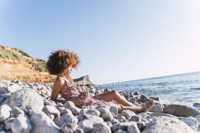 Giovane donna che indossa abito estivo e seduto sulla spiaggia di pietra — Foto stock