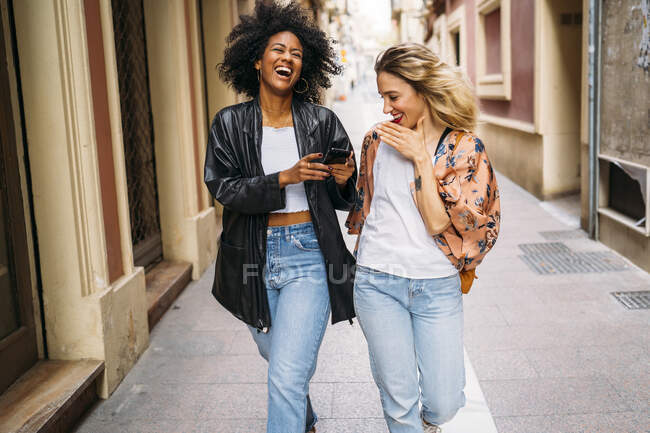 Multicultural happy women walking in the city, looking on smartphone and laughing — Stock Photo