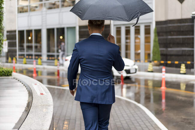 Vista trasera del joven empresario con paraguas durante un día lluvioso en Bangkok — Stock Photo