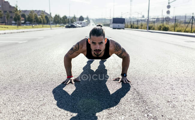 Young man doing push ups on a road — Stock Photo