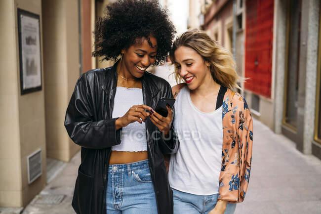 Multicultural mulheres felizes andando na cidade, olhando no smartphone — Fotografia de Stock