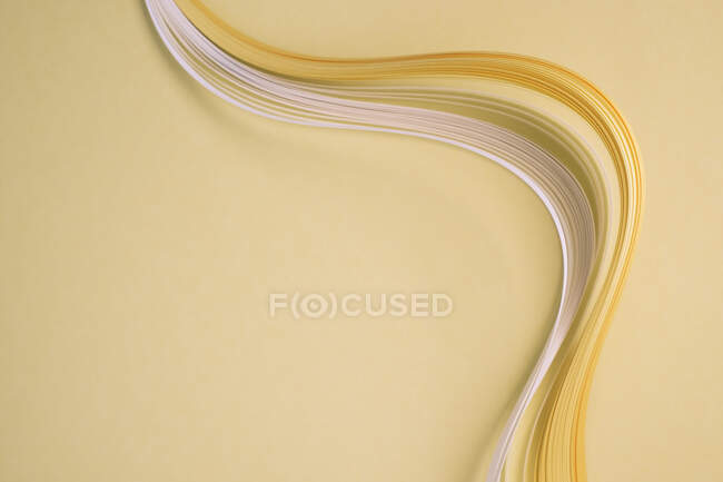 Close-up of curved quilling papers on beige background — Stock Photo