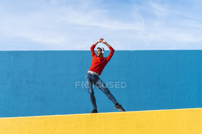 Young man with headphones, listening music, dancing on yellow wall — Stock Photo