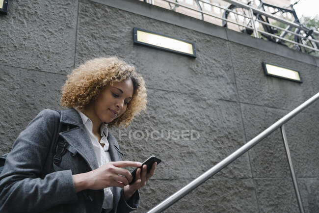Woman using smartphone at the entrance of a subway station, Berlin, Germany — Stock Photo