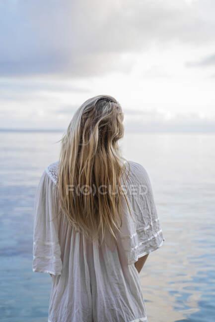 Rückansicht einer jungen blonden Frau, die vor dem Meer steht, Ibiza, Balearen, Spanien — Stockfoto