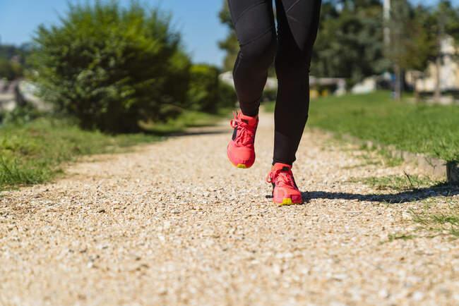 Крупный план женщины, бегущей по каменистой дорожке — стоковое фото