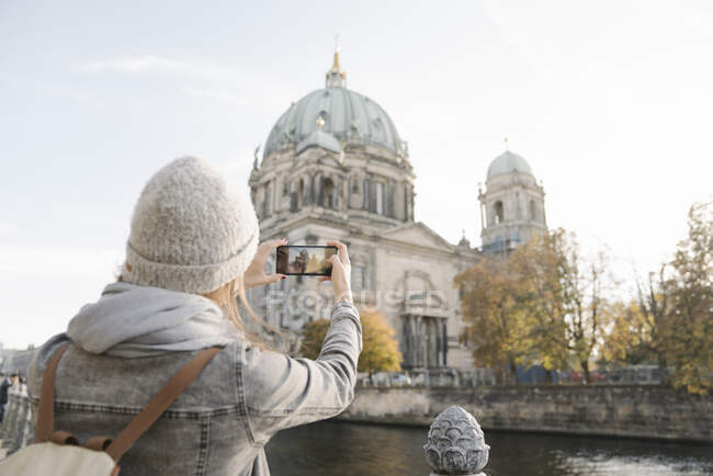 Young woman taking a smartphone picture of Berlin Cathedral, Berlin, Germany — Stock Photo