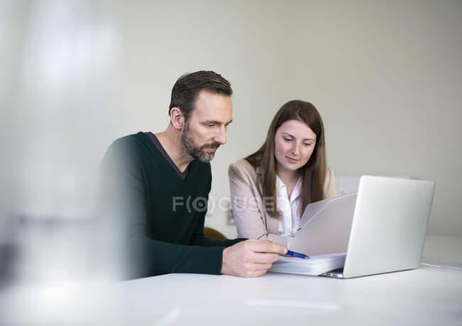 Бізнесмен і працівник з ноутбуком і документами, які працюють за столом в офісі. — стокове фото