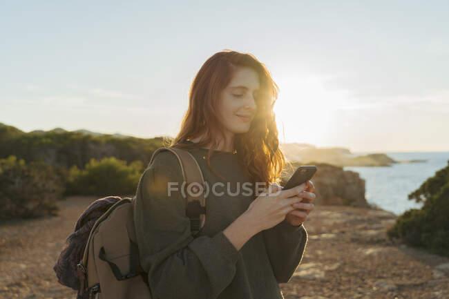 Mujer joven pelirroja usando teléfono celular en la costa al atardecer, Ibiza, España - foto de stock