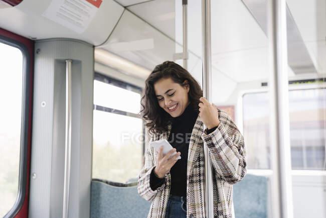 Sorridente giovane donna utilizzando smartphone su una metropolitana — Foto stock