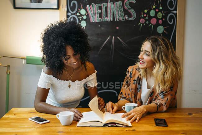 Mujeres multiculturales hablando en un café, leyendo un libro - foto de stock