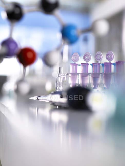 Крупный план пипетки с молекулярной структурой и пробирками на столе в лаборатории — стоковое фото