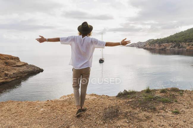Vista posteriore del giovane felice di fronte al mare, Ibiza, Isole Baleari, Spagna — Foto stock