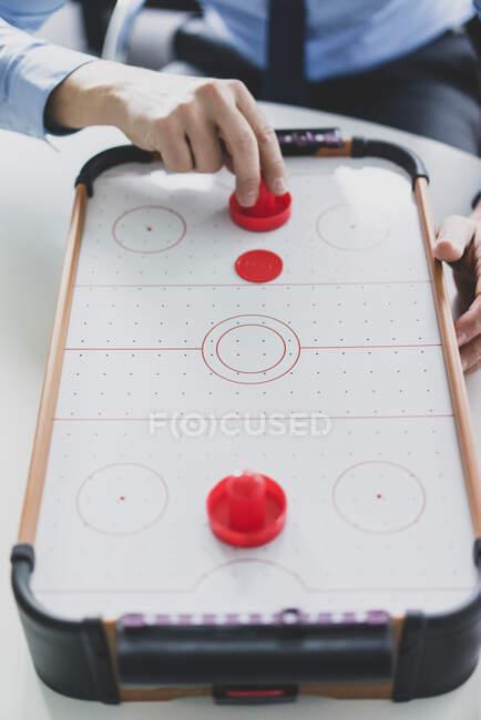 Крупный план бизнесмена, играющего в воздушный хоккей — стоковое фото