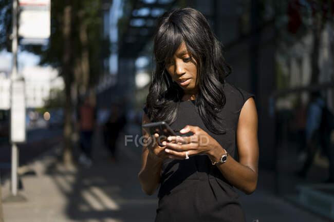 Empresaria usando smartphone en la ciudad - foto de stock