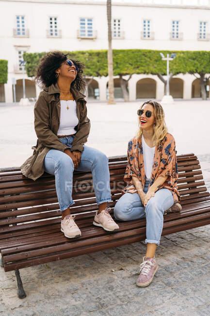 Multiculturelles femmes heureuses assis sur le banc — Photo de stock