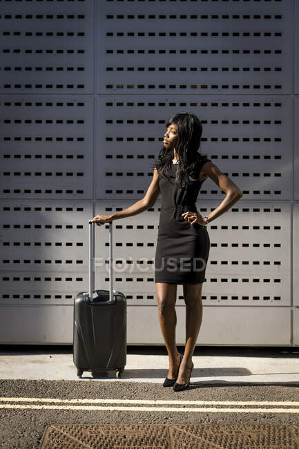 Businesswoman with trolley, looking sideways — Stock Photo