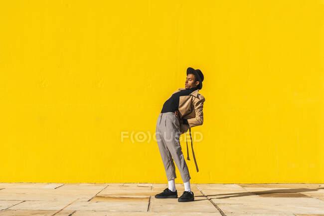 Молодий чоловік танцює перед жовтою стіною. — стокове фото