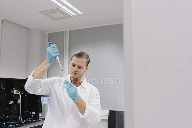 Scientist working with a pipette in laboratory — Stock Photo