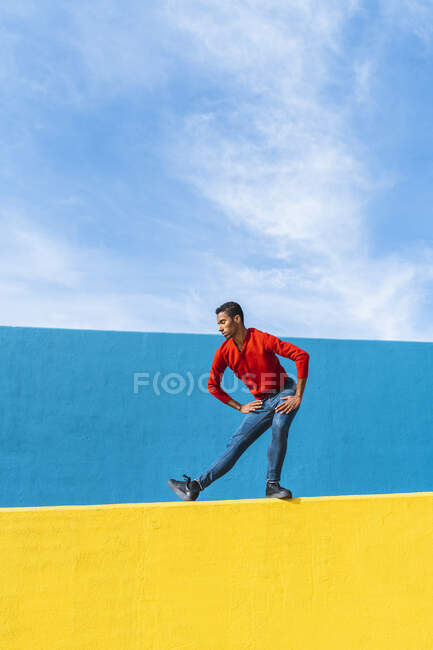 Young man dancing on yellow wall — Stock Photo