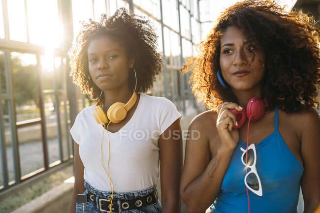 Retrato de duas jovens mulheres com fones de ouvido ao pôr do sol — Fotografia de Stock