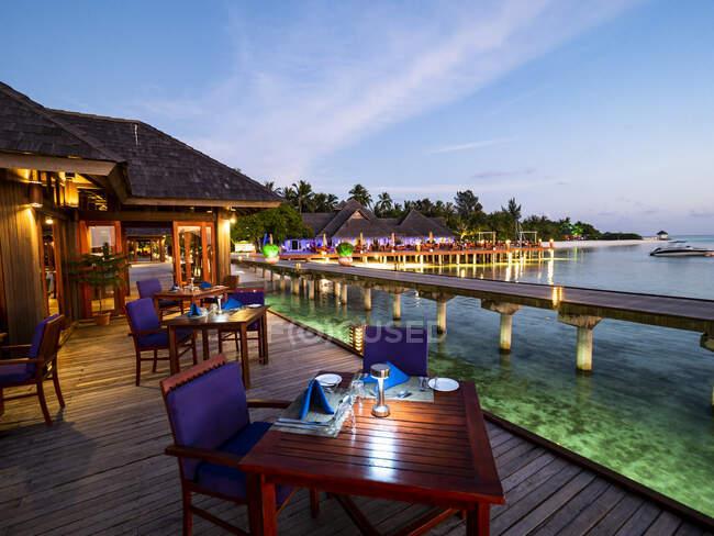 Maldive, Tavoli da pranzo del ristorante costiero al tramonto con molo sullo sfondo — Foto stock