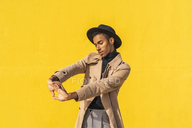 Молода танцівниця виступає перед жовтою стіною. — стокове фото