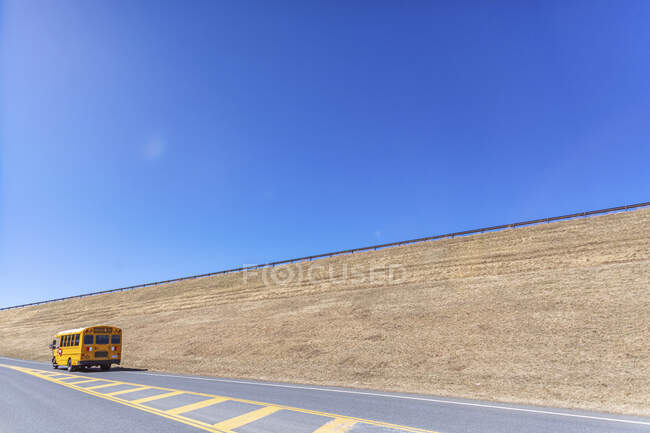 Yellow school bus moving on highway against clear blue sky — Stock Photo