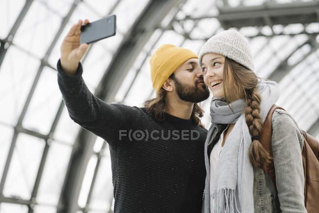 Casal jovem tirando uma selfie na plataforma da estação, Berlim, Alemanha — Fotografia de Stock