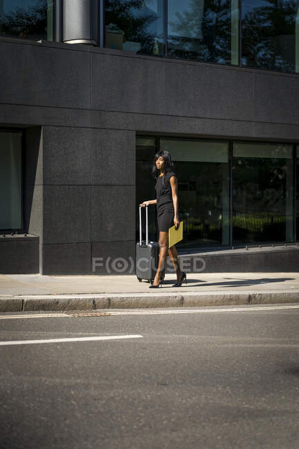 Businesswoman with trolley in the city — Stock Photo