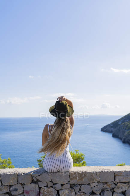 Young woman sitting on a wall and looking at distance, viewpoint in Ibiza — Stock Photo