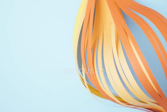 Primer plano de los papeles de extracción de color naranja sobre fondo azul - foto de stock