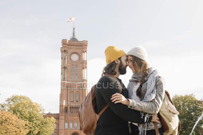 Молоде подружжя, яке обіймає Ротес Ратхаус на задньому плані (Берлін, Німеччина). — стокове фото
