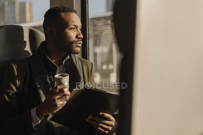 Портрет стильного бізнесмена з багаторазовим використанням чашки та документів у поїзді. — стокове фото