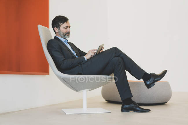 Mature businessman sitting in chair using tablet — Stock Photo