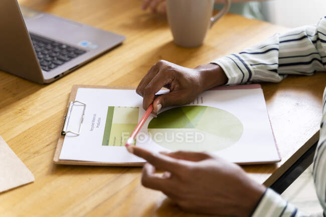 Close-up of businesswoman with document at desk in office — Stock Photo