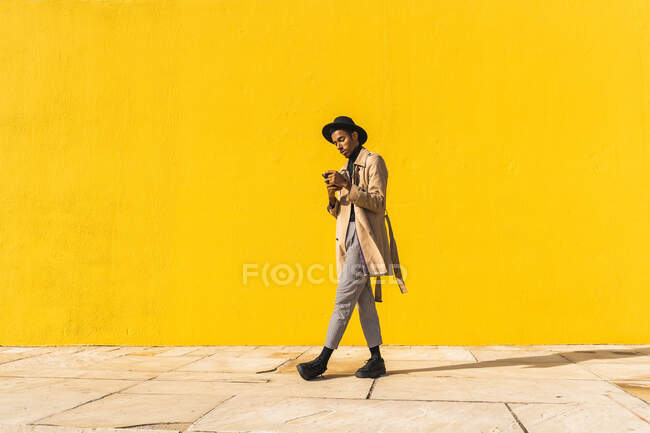 Молодий чоловік з капелюхом, користуючись смартфоном, п
