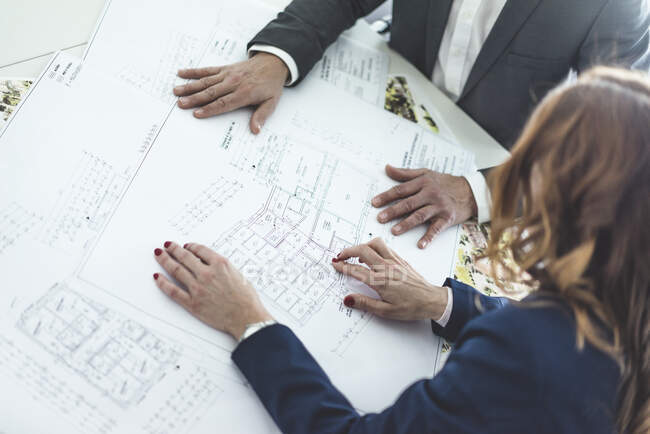 Close-up of businesswoman and businessman working on plan on desk in office — Stock Photo