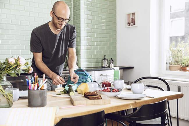 Чоловік у кухонній пакуванні закусок на обід. — стокове фото