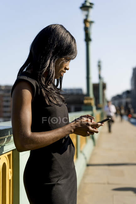 Businesswoman using smartphone on a bridge — Stock Photo