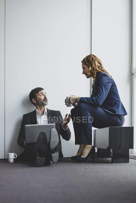 Businesswoman with businessman in office sitting on the floor using laptop — Stock Photo