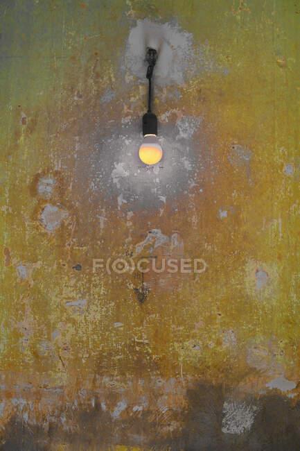 Alemanha, Berlim, Kreuzberg, Lâmpada amarela na parede velha — Fotografia de Stock