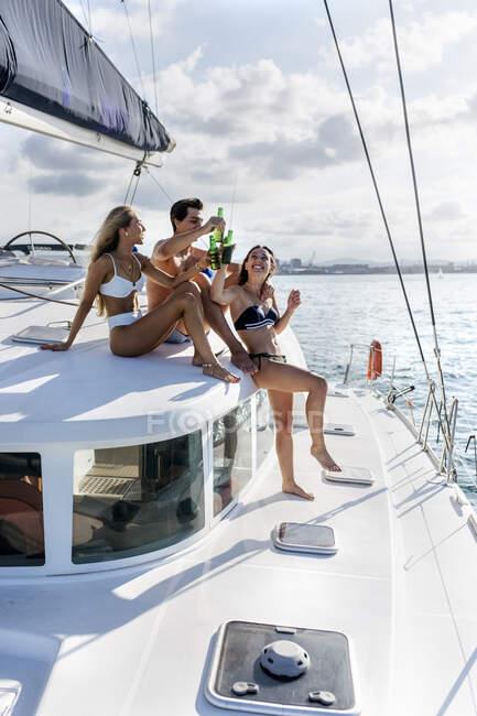 Tre giovani amici che si godono una giornata estiva su una barca a vela — Foto stock