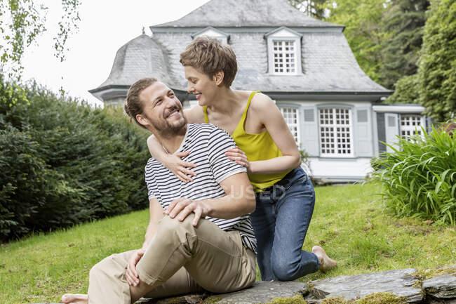 Счастливая женщина обнимает мужчину на стене в саду своего дома — стоковое фото