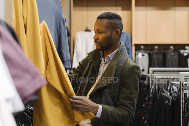Stylish man shopping in a clothes store — Stock Photo