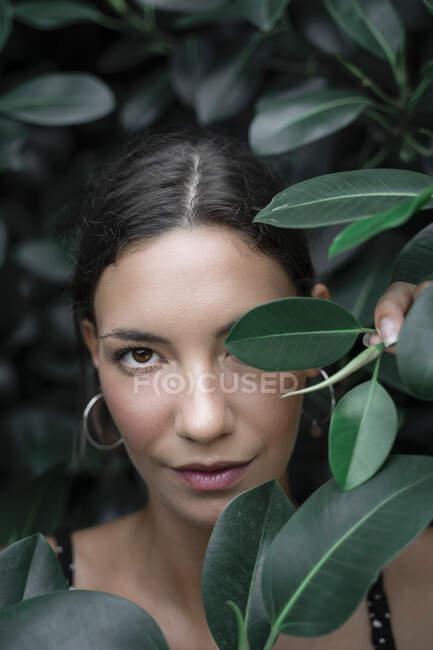Ritratto di giovane donna nascosta dietro foglie verdi — Foto stock
