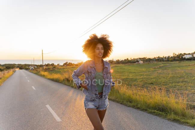 Young woman walking on street at sunset, Ibiza — Stock Photo