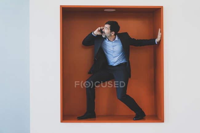 Maduro hombre de negocios en el teléfono celular atrapado en un nicho - foto de stock