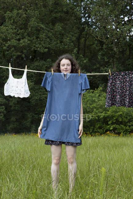 Retrato de jovem mulher de pé atrás do vestido de secagem no varal — Fotografia de Stock